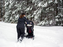 Mother Pushing Stroller in Deep Snow Royalty Free Stock Image