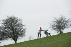 Mother Pushing Stroller Uphill In Park Royalty Free Stock Image