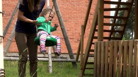 Mother pushing toddler daughter on swing in outdoor playground. stock video footage