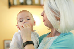 Mother put baby's pacifier in mouth. Stock Photo
