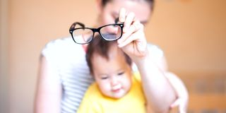 Mother put the glasses on baby, baby is laughing happy, play with mother.  royalty free stock photos