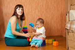 Mother puts   baby on   potty. At home Stock Images