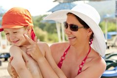 Mother puts on the baby's skin sunscreen at the beach Royalty Free Stock Photos