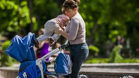 Mother Puts Baby Into Stroller In the Park stock video footage