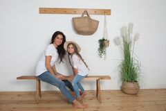 Mother puts on her little daughter a straw hat sitting on a bench in the Scandinavian style interior. Happy loving family having