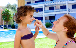 Mother puts sunscreen cream to daughter stock images