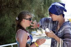 Mother puts sunscreen on her daughter's face Stock Photos