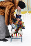 Mother puts toddler on sled Stock Photography