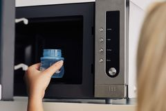 Mother putting a baby bottle into a microwave. Mother putting a baby bottle with water into a microwave Royalty Free Stock Photos
