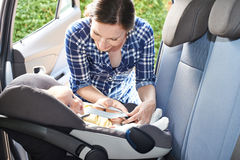 Mother Putting Baby Into Car Seat For Journey. Mother Puts Baby Into Car Seat For Journey Stock Image