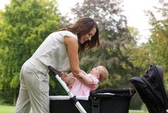 Mother putting baby into pram Royalty Free Stock Image