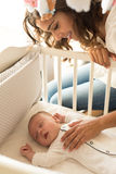 Mother putting baby to sleep Stock Photography