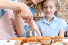 Mother putting cream on cupcakes with daughter near by Stock Photography