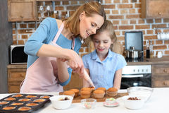 Mother putting cream on cupcakes with daughter near by Royalty Free Stock Images