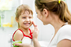Mother putting cream on her daughter's face in bathroom Stock Photos