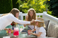 Mother putting hat on younger daughter during breakfast outdoors Royalty Free Stock Photo