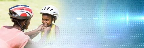 Mother putting helmet on daughter with blue smart tech transition Royalty Free Stock Photos