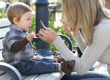 Mother putting on Make Up and Baby Boy on Street Stock Photography