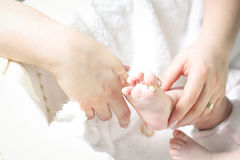 Mother putting a ring on her child's toe Royalty Free Stock Photo
