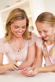 Mother putting sanitizer on young girl's hands stock images