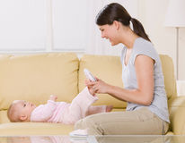 Mother putting shoes on baby on sofa at home Royalty Free Stock Photos