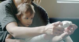 Mother putting socks on baby girl. Shot in 4K RAW on a cinema camera stock video