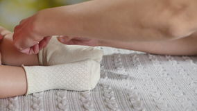mother putting socks on baby s feet white stock footage