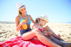 Mother putting sunscreen on back of her daughter Royalty Free Stock Image