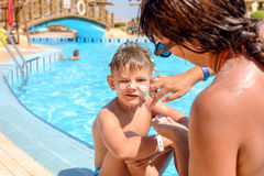 Mother putting sunscreen on her sons face Stock Photo