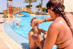 Mother putting sunscreen on her sons face Royalty Free Stock Photos