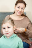 Mother raiding the hair of her child sitting in room Royalty Free Stock Images