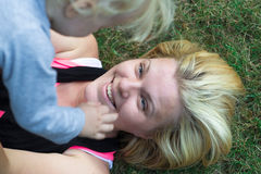 Mother raised over her child, smiling and lying on grass royalty free stock photo