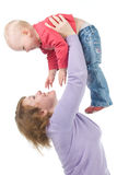 Mother raises up a cheerful daughter. Happy mother and baby . Woman raises up laughing child Stock Image