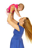 Mother raising baby girl Stock Image