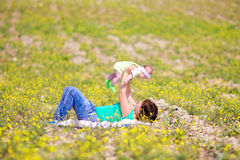 Mother raising her little daughter up Stock Photos