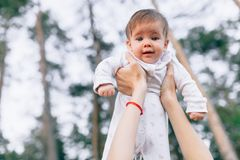 Mother hands tossing up the high air joyful baby. Outdoors healthy child activity, active lifestyle and having fun on family summe stock image