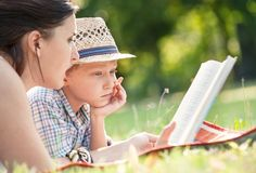 Mother read a tales for her son in summer garden Stock Photos
