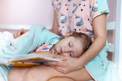 Mother is readding a book for kids good sleep. Cute mum and little girl dressed in pajamas ready for sleep at bed. Mother is readding a book for good sleep stock images