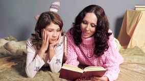 Mother reading aloud interesting storybook to her daughter, family values stock image