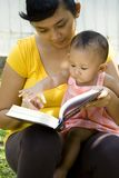 Mother reading while babysitting baby. Lifestyle portrait of Asian mother reading a book while babysitting her baby girl outdoor Royalty Free Stock Photos