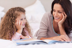 Mother reading a bedtime story for her daughter. Young mother reading a bedtime story for her daughter Royalty Free Stock Image