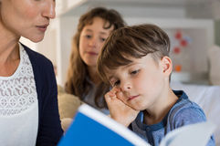 Mother reading the bedtime story. Mother reading bedtime stories with her childreen. Little boy is falling asleep while mom tells him the story. Mother helping Royalty Free Stock Photography