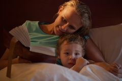 Mother reading a bedtime story to her little son. Cuddling down alongside him on the bed as he peers over the counterpane at the camera Stock Photography