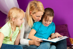 Mother is reading a book. Happy family - mother is reading a book, she and the children are sitting in a kid's room Stock Photography