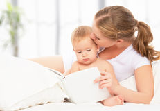 Mother reading  book baby in bed before going to sleep Stock Photo