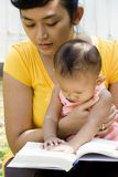 Mother reading book while babysitting. Lifestyle portrait of Asian mother reading a book while babysitting her baby girl outdoor royalty free stock photo