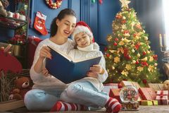 Mother reading a book at Christmas Stock Photos