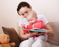 Mother is reading book with daughter Stock Image