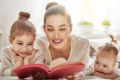 Mother reading a book. Happy loving family. pretty young mother reading a book to her daughters Stock Photos