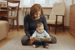 Mother reading a book with her baby Royalty Free Stock Images